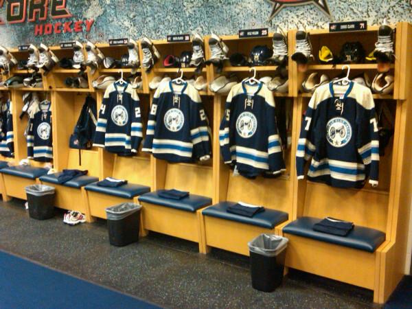 The new 3rd alternate uniforms hang in the locker stalls of the Columbus dressing room (Ryan Holtmann/CBJ)