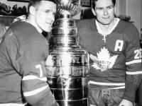 Tim Horton and teammate Allan Stanley stand next to the Stanley Cup after winning it in 1964.