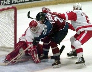 Colorado Avalanche center Peter Forsberg (21) slips past the defense of Detroit Red Wings goalie Chris Osgood, left, and center Igor Larionov for the Avalanche's fifth goal during the third period in Game 6 of the Western Conference semifinals in Detroit, Tuesday, May 18, 1999. The Avalanche defeated the Red Wings 5-2 to advance to the finals. (AP Photo/Carlos Osorio)